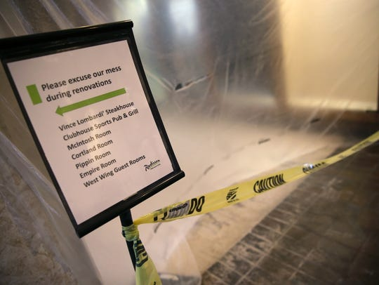 A sign points hotel guests through the lobby while a section is blocked off by caution tape and plastic during renovation at the Radisson Paper Valley Hotel.