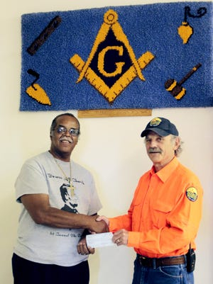 The Rev. Earseye Ross, at left, secretary of Silver City Lodge, recently presented a check for $500 to Marc Levesque, the president of Grant County Search and Rescue.