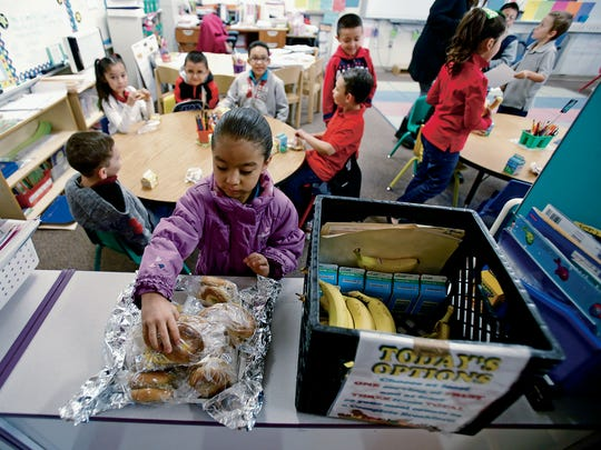 Jayleen Hernandez, 6, gets a bagle for breakfast in her first grade classroom at Ramirez Thomas Elementary School on Wednesday, Feb. 10, 2016. Breakfast after the bell serves about 115,000 kids state-wide breakfast in class after the bell rings to make up for the fact that perhaps they go to school late with no breakfast. Two state senators - Gay Kernan R-Hobbs, and Mimi Stewart, D-Albuquerque, have been taking some heat for trying to change the program to where it can be served before or after the bell to cut down on classroom disruption. But they maintain they don't want to kill the program, which is a pet project of the governor's.