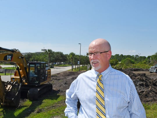 Don Walker, Brevard County communications director, stands where heavy equipment operators are working near Holy Trinity Episcopal Academy.