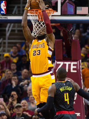 LeBron James of the Cleveland Cavaliers dunks over Paul Millsap of the Atlanta Hawks during the second half.