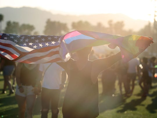 Apr 14, 2017; Indio, CA, USA; A man carries an American and rainbow flag during the Coachella Valley Music and Arts Festival at Empire Polo Club. Mandatory Credit: Richard Lui/The Desert Sun via USA TODAY NETWORK