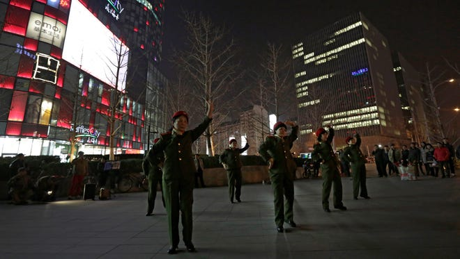 Chinese women wearing military costume dance during their daily exercises at a square outside a shopping mall in Beijing on March 24.