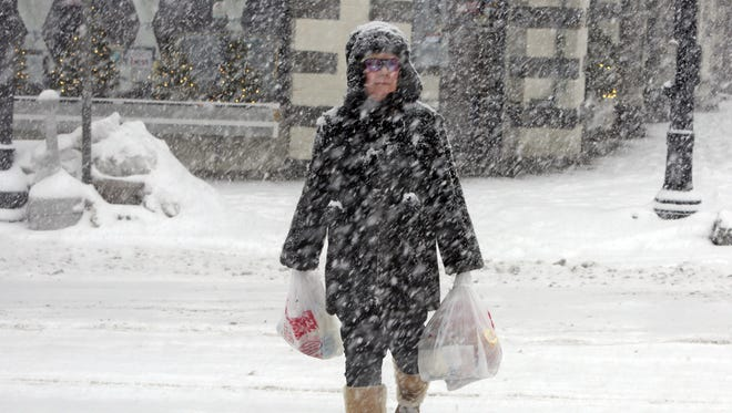 A Tarrytown resident makes her way home after walking to the supermarket to stock up on groceries during a snowstorm.