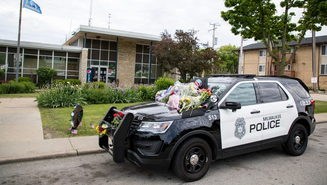 Flowers lie on a Milwaukee police squad car as part of a memorial for Officer Charles Irvine Jr., who was killed in a crash while pursuing a reckless driver last year.