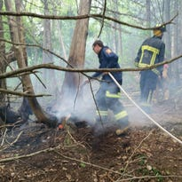 Firefighters battle a blaze on Eagle Mountain in Milton on Friday morning.