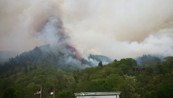 Several firefighters battle a wildfire near Hot Springs.