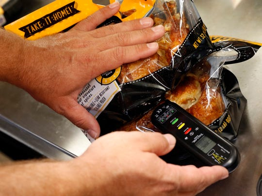 Kevin Barlow stacks two roasted chickens on top of one another to get a temperature reading without opening the package Wednesday morning, June 27, 2018, at the Kroger grocery store on North Memorial Drive in Lancaster.