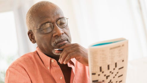 Elder man doing crossword puzzle
