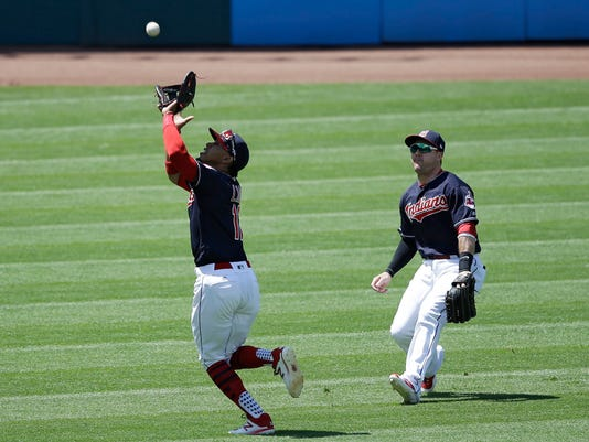 Cleveland Indians' Francisco Lindor, left, catches a ball hit by Minnesota Twins' Eduardo Escobar in the fifth inning of a baseball game, Sunday, June 25, 2017, in Cleveland. Daniel Robertson watches. Escobar was out on the play. (AP Photo/Tony Dejak)