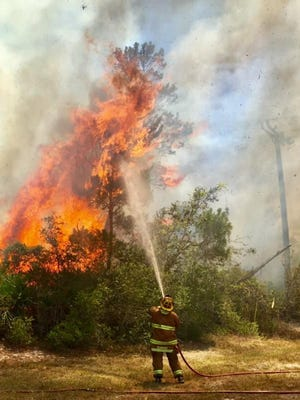 Firefighters battle a wildfire March 23, 2018, near Southeast Bakersfield Street and Southeast Montrose Lane in St. Lucie County.
