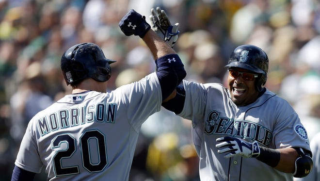 Seattle Mariners' Nelson Cruz, right, is congratulated by teammate Logan Morrison (20) after hitting a three-run home run in the eighth inning of a baseball game against the Oakland Athletics, Saturday, April 11, 2015, in Oakland, Calif.