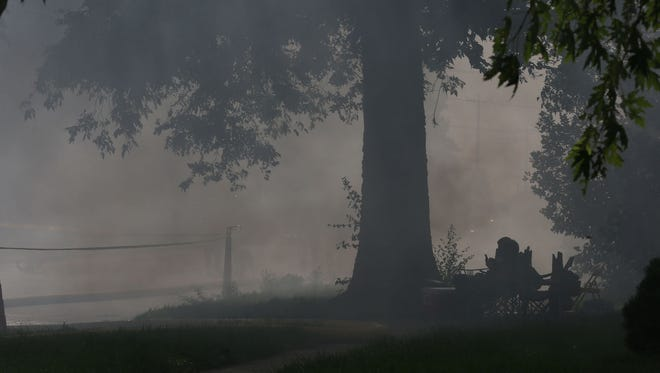 Spectators get smoked out while watching a controlled burn of a house on Lincoln St. in Bondurant Sunday which was done to make extra room for a parkSunday, Aug. 24, 2014.