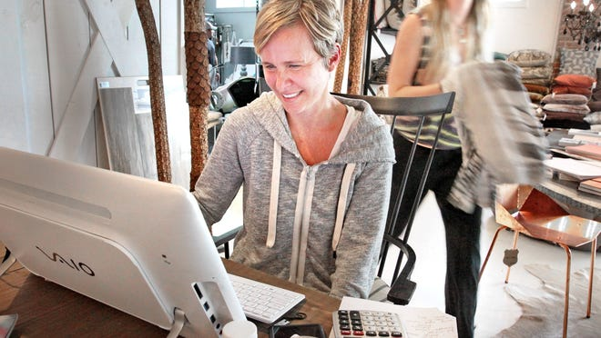 Owner, Heidi Woodman, works at the computer in the part of the showroom that also serves as the shop's office at Haus Love.