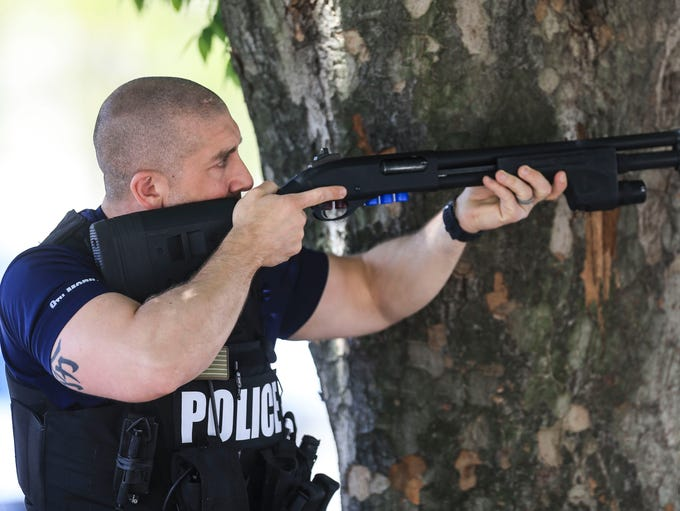 A Louisville Metro police detective uses a tree as