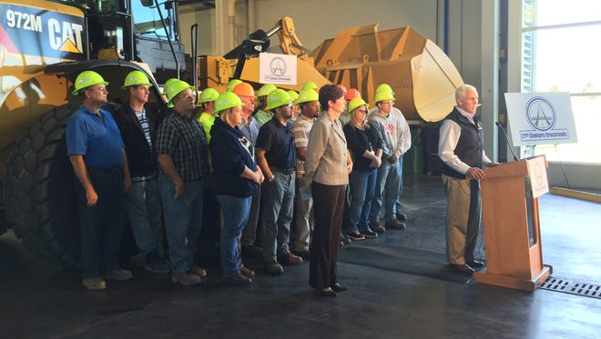 INDOT workers pose behind Gov. Mike Pence Tuesday, Oct. 13, 2015, as he announces his road-fix plan.