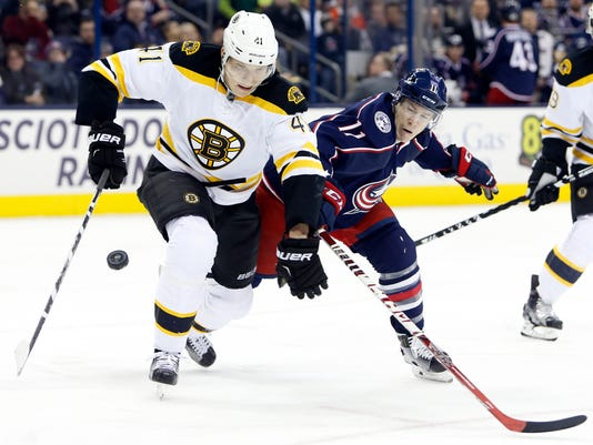 Boston Bruins' Joonas Kemppainen, left, of Finland, and Columbus Blue Jackets' Matt Calvert chase a loose puck during the second period of an NHL hockey game Tuesday, Feb. 16, 2016, in Columbus, Ohio. (AP Photo/Jay LaPrete)