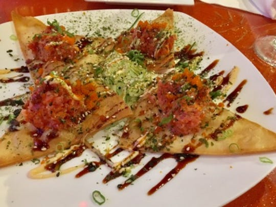 Sushi nachos are four large fried flour tortilla chips