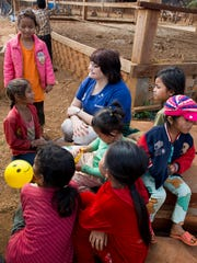 Kiwanis International President Sue Petrisin reads to children during a trip to Cambodia in February.