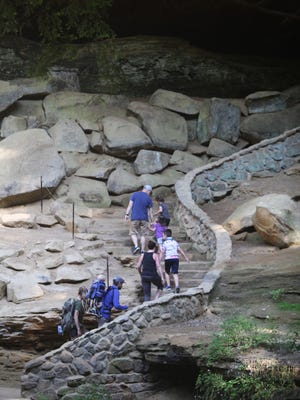 Hikers enjoy the newly reopened trail yesterday morning at Old Man's Cave in Hocking Hills State Park.