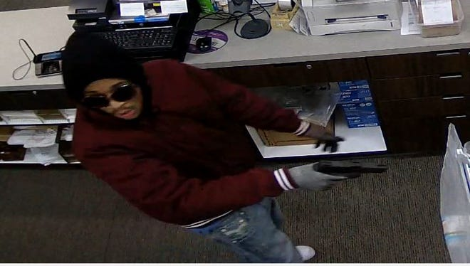 A suspect in an armed robbery of Swan Pharmacy, 9130 W. North Aveon, holds up a gun Wednesday.