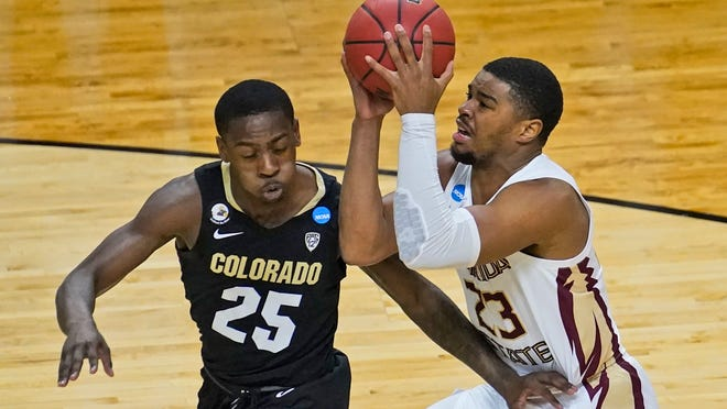 Florida State guard M.J. Walker (23) drives to the basket as Colorado guard McKinley Wright IV (25) defends during the second half of a second-round game in the NCAA college basketball tournament at Farmers Coliseum in Indianapolis, Monday, March 22, 2021. (AP Photo/Charles Rex Arbogast)