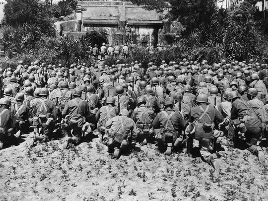 Fighting men of the 165th regiment, 2nd battalion of the 27th division kneel during memorial services for the late President of the United States, Franklin Delano Roosevelt on Okinawa on April 21, 1945.