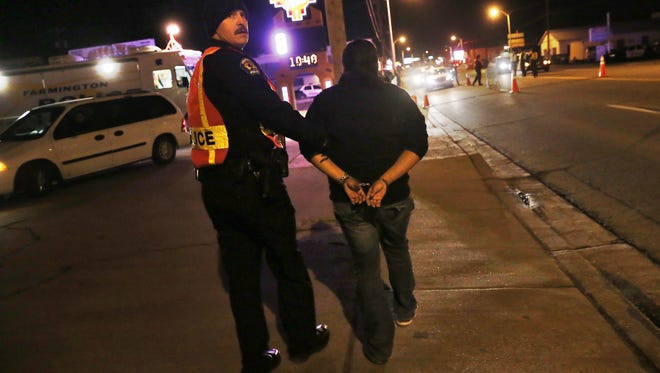 Officer William Temples with the Farmington Police Department takes a woman into custody in December 2014 at a sobriety checkpoint on East Main Street in Farmington.