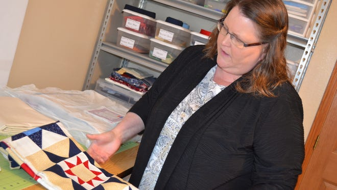 Jill Bothe looks over a quilt top made by the Grateful Valor Girls that will be sent, along with a backing, reto a longarmer, who will sew the quilt together. After that, it will be returned to Bothe and then presented to a veteran that has been touched by war.