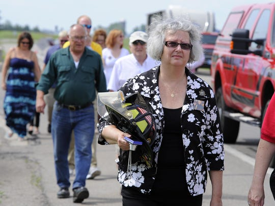 Widow Marie Sanborn carries husband Tim Sanborn's firefighting helmet to dedication ceremonies for the Tim Sanborn Memorial Highway dedication on US 127 north of St. Johns Monday. Sanborn, of Clinton Area Fire and Rescue, died in 2007 of a heart attack while operating pumps at the scene of a fire.