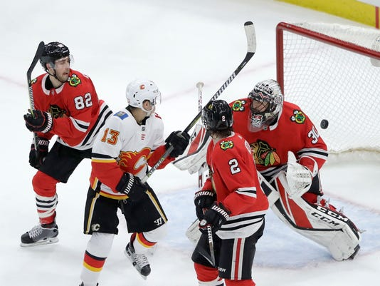 Calgary Flames' Johnny Gaudreau (13) watches a shot from teammate Michael Stone go past Chicago Blackhawks goaltender Jeff Glass for a goal, as Jordan Oesterle (82) and Duncan Keith also watch during the third period of an NHL hockey game Tuesday, Feb. 6, 2018, in Chicago. The Flames won 3-2. (AP Photo/Charles Rex Arbogast)