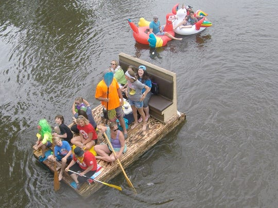 A homemade raft and inflatable cruise down the Kalamazoo River at the Battle Creek Metropolitan Moustache Society Raft Race on Saturday, June 23, 2018.