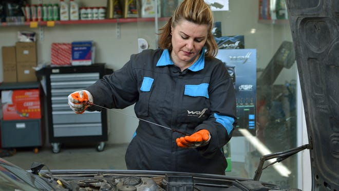 Shadi Mohammed works on a customer's car in her garage staffed by women in the Iraqi city of Sulaimani.