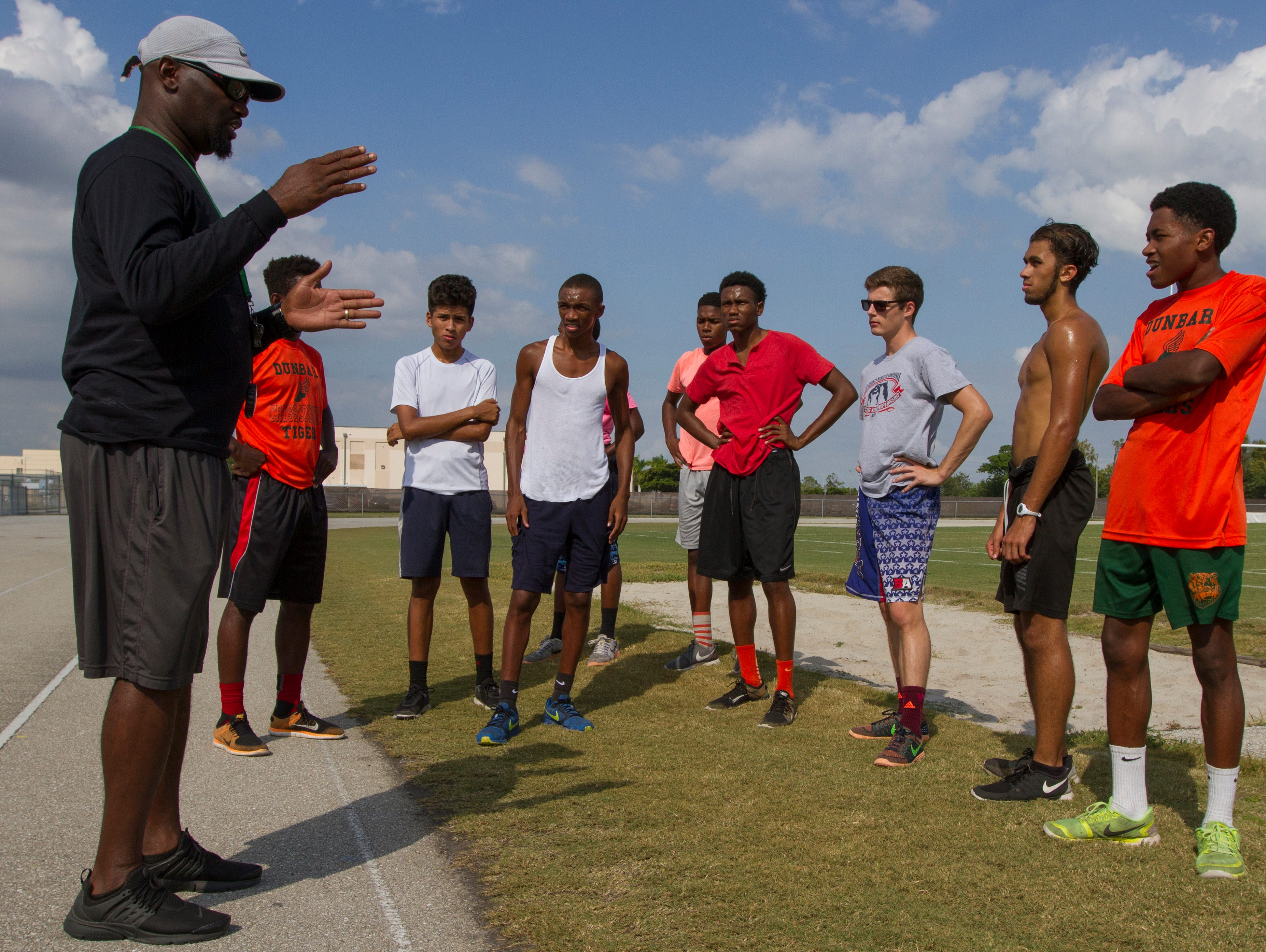 Cross country coach Guy Thomas,left, works with members of his Dunbar High School cross country team Wednesday, November 2, in Fort Myers. The team has qualified for its first state championship in school history.