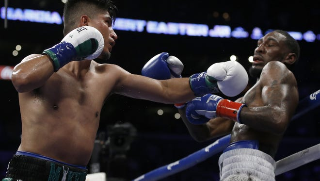 Mikey Garcia, left, hits Robert Easter Jr. with a left during the 12th round of their WBC and IBF lightweight title bout at Staples Center on Saturday night. Garcia won by unanimous decision.