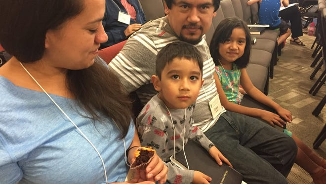 Eliseo Jimenez and his family participate in a church service at Umstead Park United Church of Christ in Raleigh, N.C. From left, Gabriela, Christopher, Eliseo and Alison.