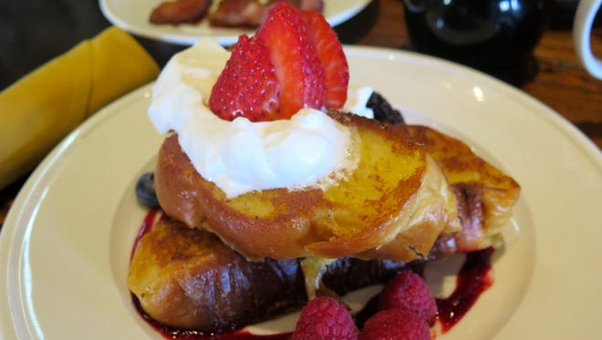 The Challah French Toast at 150 Sunset is served with two egg-battered slices of toast, served on a bed of berry gastrique and topped with Chantilly cream and berries.