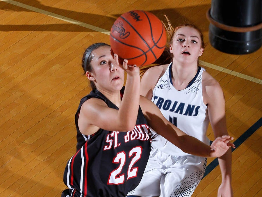 St. Johns' Erika Ballinger (22) puts up layup in front of East Lansing's Taryn McCutcheon Tuesday, Jan. 26, 2016, in East Lansing, Mich.