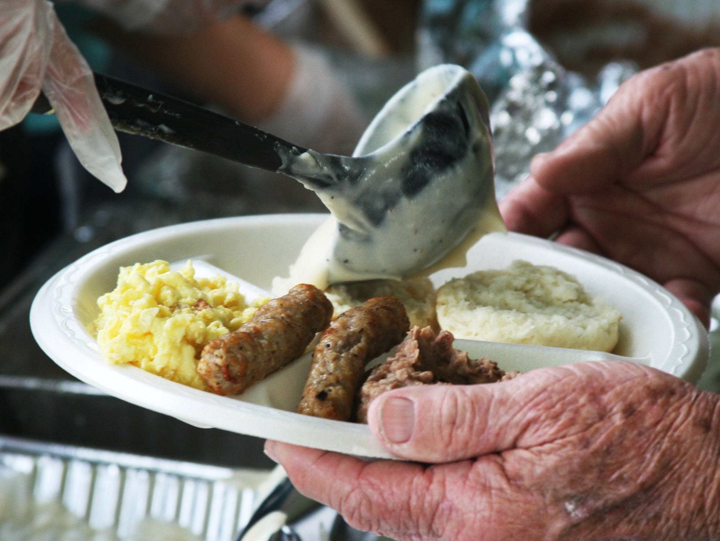 A volunteer ladles gravy over the biscuits during the