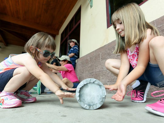 Shyla Moreno, 2, left, and her sister Elizabeth Najvar, 8, roll a tin can back and forth while making ice cream on Sunday during the 14th annual Ice Cream Sunday event at the Southern New Mexico Heritage Museum.