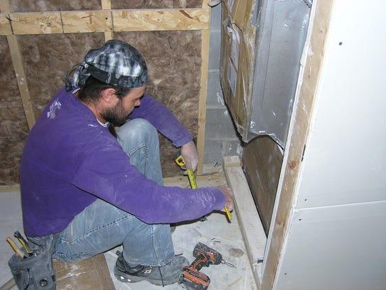 Phil Braaten of Denkins Drywall, Kaukauna, works on
