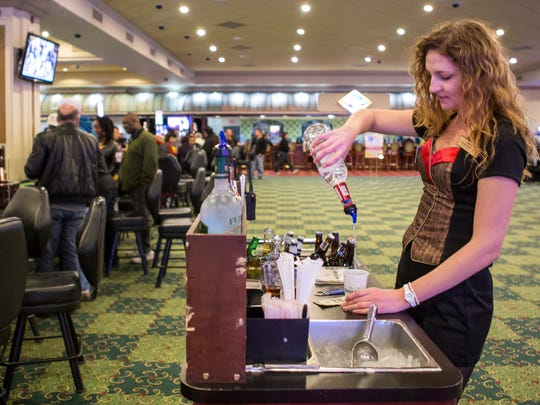 Ashley Rogers mixes a drink for gamblers at black jack