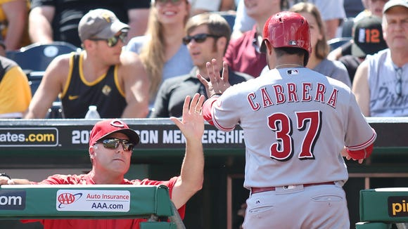 Cincinnati Reds catcher Ramon Cabrera (37) is greeted by manager Bryan Price (left) after scoring a run against the Pittsburgh Pirates during the second inning at PNC Park.