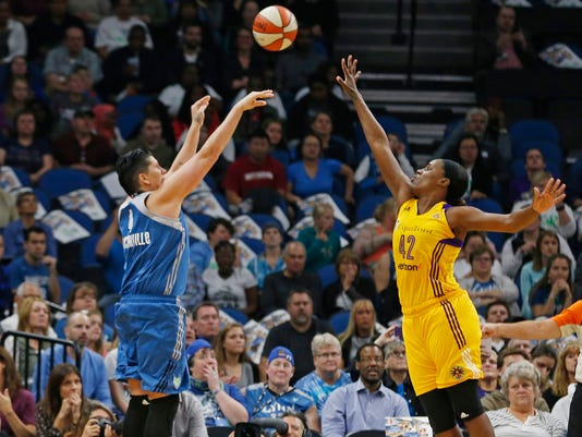FILE - In this Oct. 11, 2016, file photo, Minnesota Lynx's Janel McCarville shoots and scores over Los Angeles Sparks' Jantel Lavender during the first quarter of Game 2 of the WNBA basketball finals in Minneapolis. Coming off one of the most successful seasons in WNBA history on and off the court, the league has found ways to try to bring in new fans. Whether streaming games on Twitter, partnering with FanDuel to offer daily fantasy sports or just having more games on television, the WNBA is growing. (AP Photo/Jim Mone, File)
