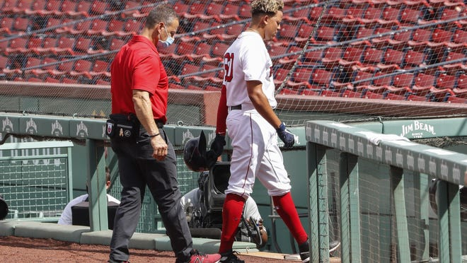 The Red Sox' Yairo Munoz heads into the dugout with a trainer after being injured while running out a single against the  Blue Jays in the first inning of Sunday's game. He suffered an apparent hip injury.