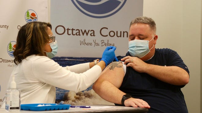 Ottawa County Department of Public Health immunization nurse Robin Schurman administers the Pfizer/BioNTech COVID-19 vaccine to Jeff Potter, Zeeland firefighter and EMT, on Friday, Dec. 18 at Grand Valley State University's Holland campus where a vaccine clinic has been set up.