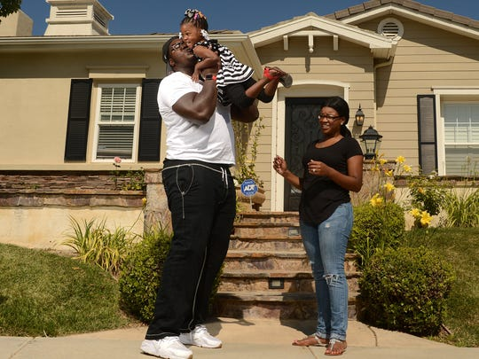 The Los Angeles Rams' Jamon Brown, shown in 2016 with his daughter Micayla, and wife Micquel Brown, pose in front of their Dos Vientos home in Newbury Park.