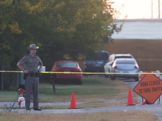A Texas state trooper stands in front of a closed road leading to First Baptist Church in Sutherland Springs, Texas. In all, 26 people were shot to death at the church on Nov. 6, 2017. Authorities say the gunman also was killed.