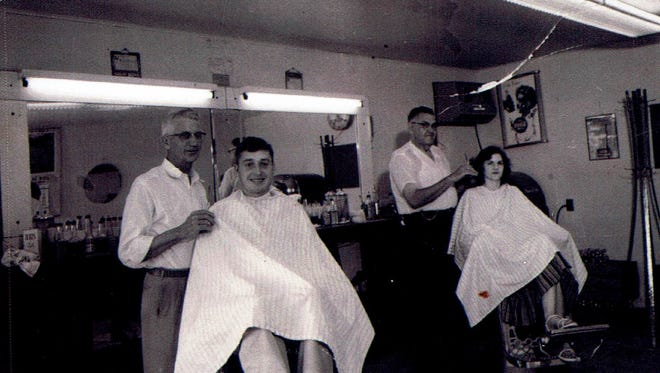 Dudley Brooks cuts hair in Brooks and Mann Barber Shop in Erin, c. 1963.