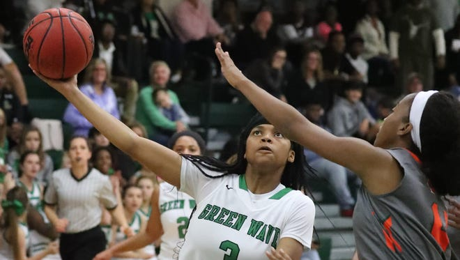 Fort Myers' Destanni Henderson gets past Dunbar's Radajah Young to score in the first half of their game.  Dunbar played at Fort Myers for the girls basketball game.